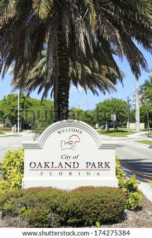 OAKLAND PARK, FLORIDA - MAY 7, 2013: Large beige cement sign with black lettering in the median on NE 38th Street headed west into the city with a population of 42,832 in 2012 on a sunny spring day.  - stock photo