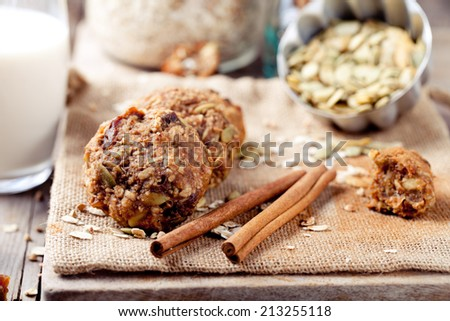 Oat and peanut butter cookies with pumpkin seeds and cinnamon with a glass of milk on a wooden background. - stock photo