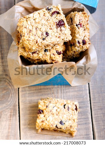 Oat bars with cranberry, nuts and seeds in a box, selective focus on the top slice