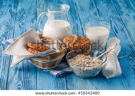Oat cookies and milk on blue wooden table - stock photo