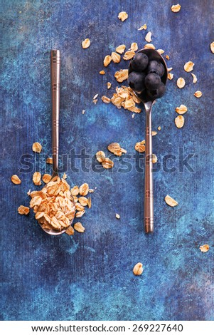 Oat flakes and fresh blueberry in vintage spoons on blue grunge wooden background - stock photo