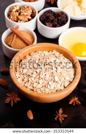 oat flakes and ingredients on a black table, top view, close-up, vertical