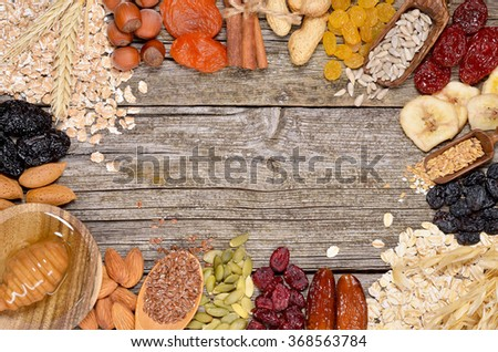 Oat flakes and various delicious ingredients for breakfast. Ingredients for homemade granola. Copyspace background. Top view. - stock photo