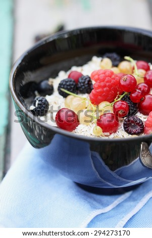 oat flakes in a bowl with fresh berries - stock photo