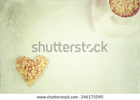 Oat flakes in a shape of heart and cup with saucer - stock photo