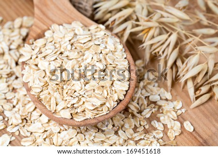 oat flakes in a spoon on wooden surface - stock photo