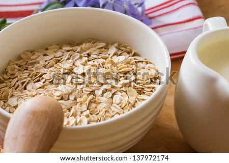 Oat flakes in orange bowl  on wooden table. Selective focus.