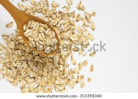 Oat flakes in spoon on oat flakes background with empty place for your text. - stock photo