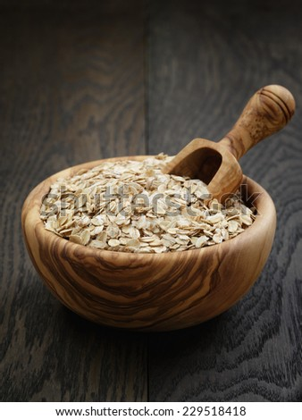 oat flakes in wood bowl on oak table, rustic style - stock photo