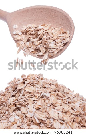 oat-flakes is poured from the wooden spoon - stock photo