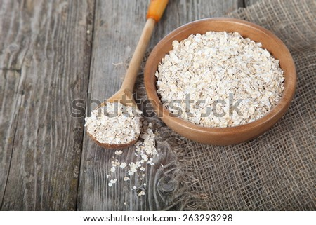 Oat flakes on old wooden table. - stock photo