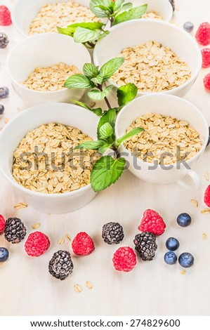 oat flakes pile  in white bowls with mint and fresh summer berries - stock photo