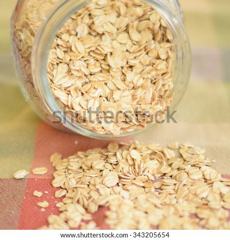 Oat flakes spilled out from glass jar - stock photo