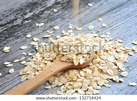 Oat flakes spilling in a wooden spoon on old wooden background - stock photo