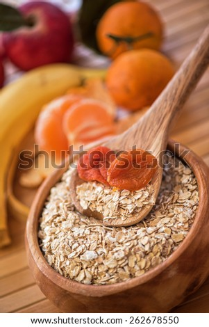 Oat flakes with  dried apricots at wooden plate on wooden background - stock photo