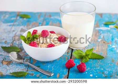 Oat flakes with milk and fresh raspberries for breakfast, glass with milk, spoon, fresh mint on an old wooden blue background. The concept of a healthy diet, weight loss - stock photo