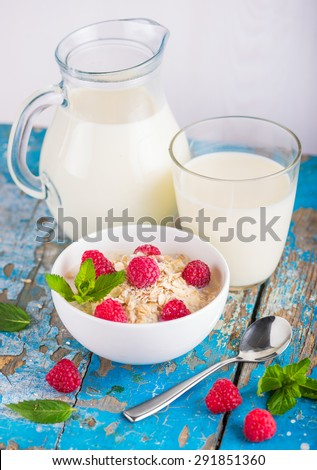 Oat flakes with milk and raspberries for breakfast, glass with milk, jar, spoon,  fresh mint on an old wooden blue background, the concept of a healthy diet, weight loss - stock photo