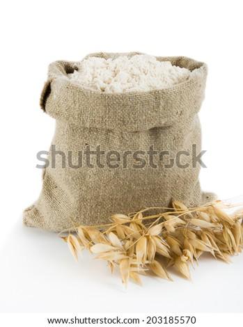 Oat flour in small linen sack - stock photo