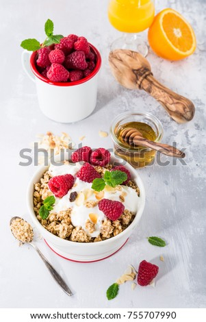 Oat granola with berries and yoghurt on light gray background. Healthy breakfast concept.