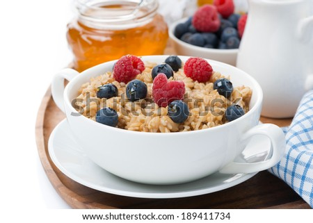 oat porridge with berries and honey, close-up, isolated on white