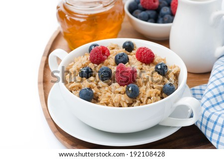 oat porridge with fresh berries and honey, close-up, isolated on white