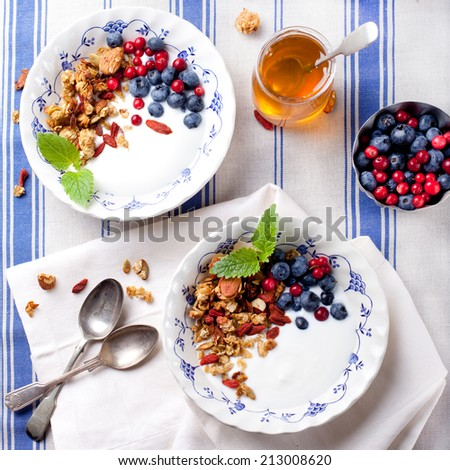 Oat, pumpkin seeds and goji berries granola with honey and fresh berries in blue and white ceramic bowls on a textile background. - stock photo