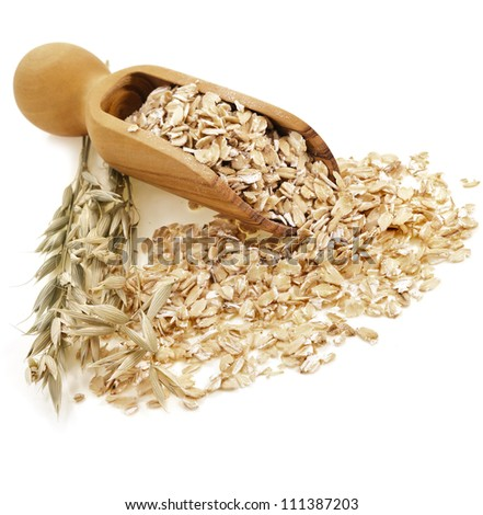 Oat rolled flakes with wooden scoop on white background