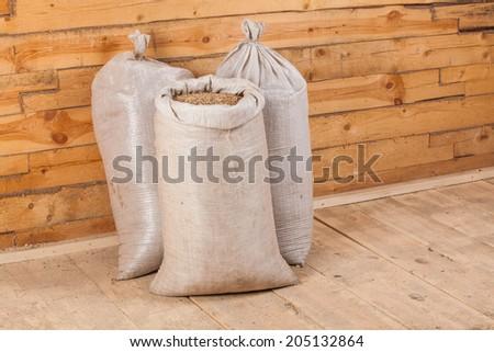 oat seed grain in burlap sack bag on wooden farm - stock photo