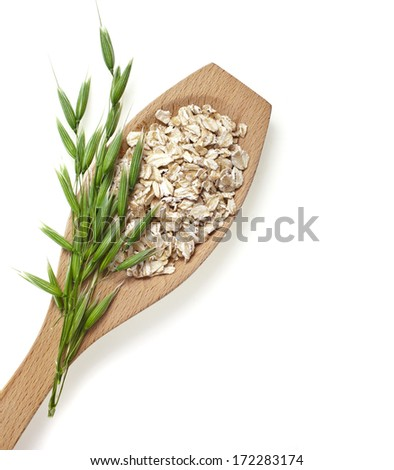 oat seeds close up in wooden spoon surface texture isolated on white background  - stock photo