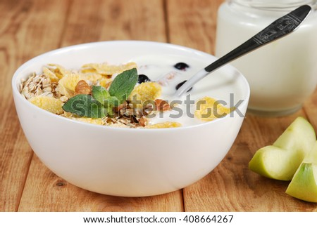 Oat, wheat and corn flakes with nuts, yogurt and mint leaves in a small white bowls on a wooden background