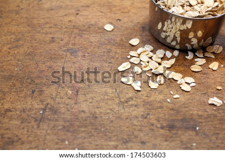 oatmeal and measuring cup over old wood background