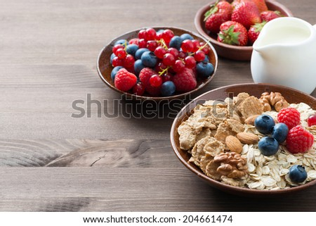 oatmeal and muesli in a bowl, fresh berries and milk on wooden background (with space for text), horizontal - stock photo