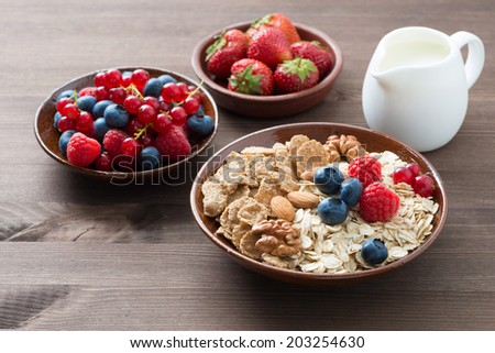 oatmeal and muesli in a bowl, fresh berries and milk on wooden table, horizontal - stock photo