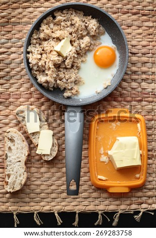 oatmeal breakfast with scrambled eggs and bread and butter on the table - stock photo