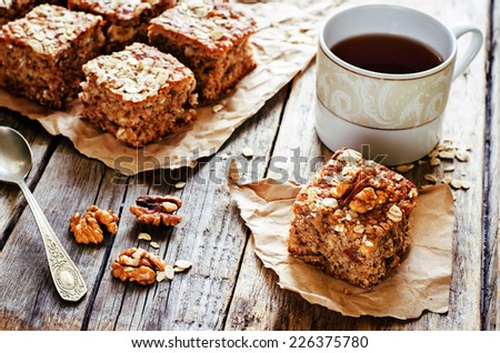 oatmeal cake with dates and walnuts on a dark wood background. tinting. selective focus on walnut