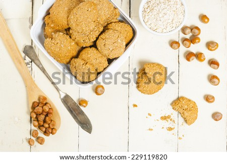 oatmeal cookie chips with hazelnuts on old white wood background - stock photo