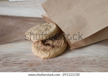 Oatmeal cookie with brown paper bag on wood