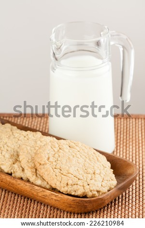 Oatmeal Cookies - A set of fresh, homemade oatmeal cookies on a wooden tray served with milk. Shallow Depth of Field. - stock photo