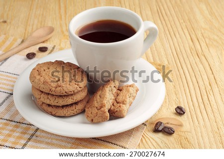 Oatmeal cookies and cup of black coffee on wooden table