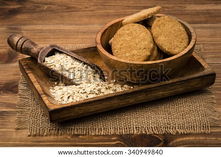 Oatmeal cookies and flakes on the wooden plate on the rustic surface.