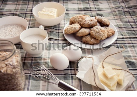 Oatmeal cookies  and ingredients on the checkered tablecloth. Top view