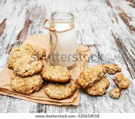 oatmeal cookies and  milk on a old wooden background - stock photo