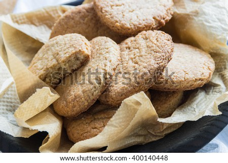 Oatmeal cookies in wooden plate - stock photo