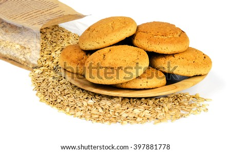Oatmeal cookies on a wooden plate and a paper bag with crumbled oat flakes, isolated on white background. - stock photo