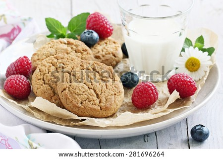 Oatmeal cookies with milk and fresh berries.Selective focus - stock photo