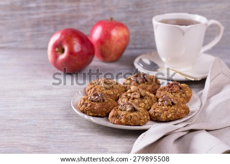 Oatmeal cookies with walnuts, apples and a cup of tea on a wooden surface - stock photo