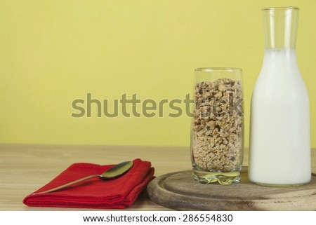 oatmeal flakes in a glassful next to the milk carafe. Healthy breakfast with fiber. Fresh milk in the glass and muesli breakfast - stock photo