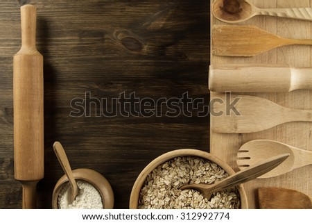 oatmeal flakes in a wooden bowl with a spoon, ears of wheat, pot of flour, kitchen utensils on the table. homemade, menu, recipe, mock up.