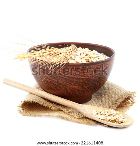 Oatmeal flakes in wooden bowl isolated on white background. Healthy food.  - stock photo