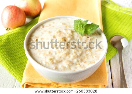Oatmeal fresh hot simple porridge with mint on napkin and wooden table. Natural healthy vegetarian breakfast, close up, horizontal. - stock photo